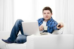 Relaxed man using Computer at home switching tv on Stock Photo