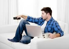 Relaxed man using Computer at home switching tv on. Attractive relaxed man with Computer at home switching tv on Stock Photos