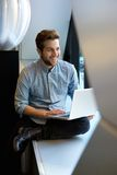 Relaxed man using laptop. Portrait of a happy relaxed man using laptop Royalty Free Stock Photo