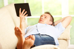 Relaxed man using tablet Stock Photos