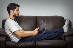 Relaxed man using a tablet in the living room . Sitting on the s stock image
