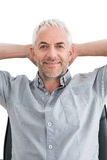 Relaxed mature businessman with hands behind head Stock Photography