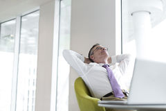 Relaxed mature businessman reclining at lobby Stock Image