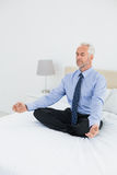 Relaxed mature businessman sitting in lotus posture on bed Stock Photos