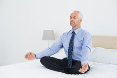 Relaxed mature businessman sitting in lotus posture on bed Stock Photo