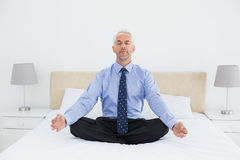 Relaxed mature businessman sitting in lotus posture on bed Stock Photography