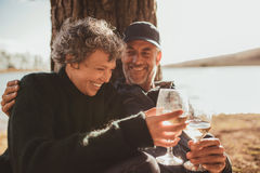 Relaxed mature couple having a glass of wine at campsite. Portrait of relaxed mature couple having a glass of wine at campsite. Senior men and women toasting stock photo
