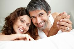 Relaxed mature couple lying on bed smiling Royalty Free Stock Photos