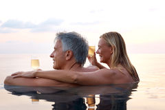 Relaxed mature couple in pool with drinks Royalty Free Stock Image