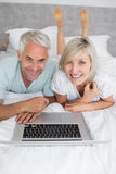 Relaxed mature couple using laptop in bed Royalty Free Stock Photo