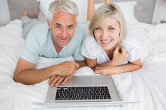 Relaxed mature couple using laptop in bed Stock Photos