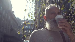 Relaxed mature guy standing outdoors and drinking coffee stock video