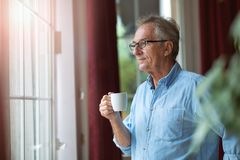Free Relaxed Mature Man At Home Standing By The Window Royalty Free Stock Photos - 156928298