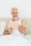 Relaxed mature man reading book in bed Royalty Free Stock Image