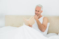 Relaxed mature man reading book in bed Royalty Free Stock Photography