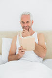 Relaxed mature man reading book in bed Royalty Free Stock Images