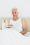 Relaxed mature man reading book in bed Stock Image