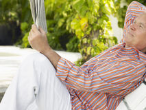 Relaxed Mature Man Reading Newspaper On Lounge Chair Stock Photography