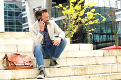 Relaxed mature man talking on cell phone. Portrait of relaxed mature man sitting outside on stairs and talking on cell phone Royalty Free Stock Photo