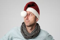 Relaxed mature man wearing santa claus hat looking aside on grey background Royalty Free Stock Photos