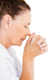 Relaxed mature woman praying. Mature woman praying against white background royalty free stock photo