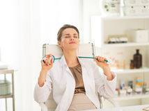 Relaxed medical doctor woman sitting in office Royalty Free Stock Image