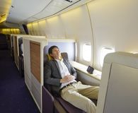 Relaxed mid adult business man sleeping in first class seat.  Royalty Free Stock Photo