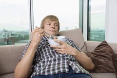 Relaxed mid-adult man with bowl of cereal in living room at home Royalty Free Stock Photo