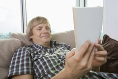 Relaxed mid-adult man reading book in living room at home Royalty Free Stock Image