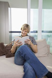 Relaxed mid-adult man reading book in living room at home Stock Photo