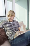 Relaxed mid-adult man reading book in living room at home Stock Image