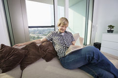 Relaxed mid-adult man reading book in living room at home Stock Photography