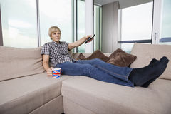 Relaxed mid-adult man watching television while having coffee on sofa at home Stock Photography