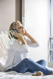 Relaxed mid adult woman listening music through headphones on bed Royalty Free Stock Photo
