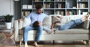 Relaxed millennial couple lounge on couch using laptop together