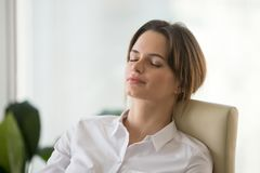 Relaxed calm mindful woman resting on comfortable office chair royalty free stock photos