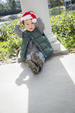 Relaxed Mixed Race Boy Wearing Christmas Santa Hat. Cute Mixed Race Boy Sitting At The Park Wearing Christmas Santa Hat Royalty Free Stock Photo