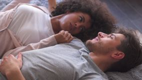 Relaxed couple talking in bed stock footage