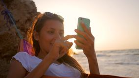 Relaxed mixed race young woman using mobile phone in hammock at the beach near the sea against stunning golden sunset stock footage