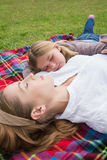 Relaxed mother and daughter lying at park Royalty Free Stock Images