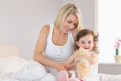 Relaxed mother and daughter sitting on bed Royalty Free Stock Photography