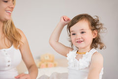 Relaxed mother and daughter sitting on bed Royalty Free Stock Photos