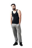 Relaxed muscular athlete with hands in pockets looking at camera Royalty Free Stock Photos