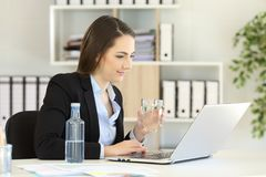Office worker working holding a water glass. Relaxed office worker working on line with a laptop and holding a water glass Stock Photography