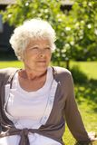 Relaxed old lady sitting outdoors Royalty Free Stock Photography