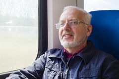 Relaxed old man sitting near the window. In the carriage Stock Photo