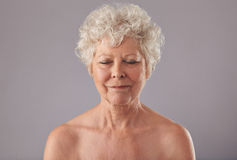 Relaxed old woman in thought. Close-up of relaxed old woman on grey background with her eyes closed in thought. Naked senior female against grey background Royalty Free Stock Image