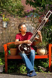 Relaxed older man is playing a sitar Stock Image