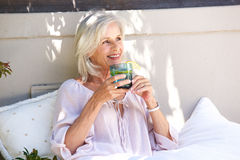 Relaxed older woman outside drinking tea with lemon Stock Image