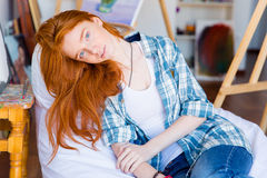 Relaxed pensive female lying on white beanbag in art studio Royalty Free Stock Photography